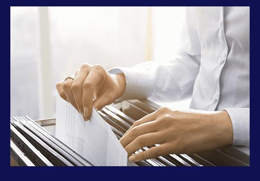 Eine Frau sucht Unterlagen in einem Aktenschrank