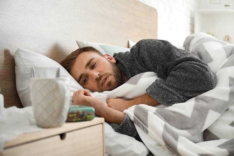 Mann mit Erkaltung liegt im Bett