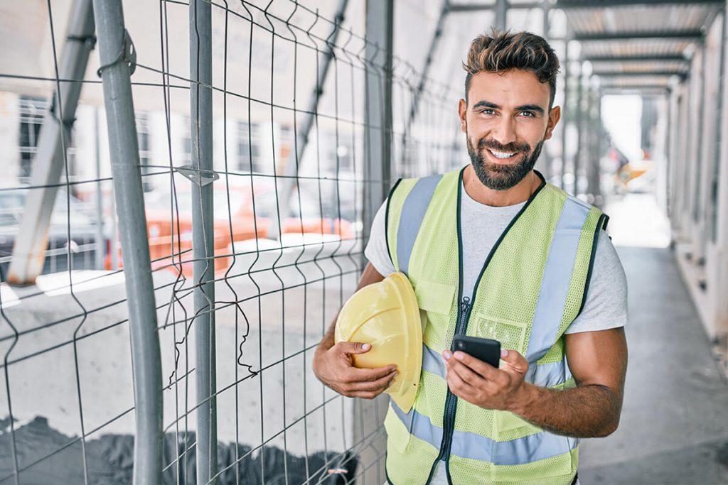 Mann nutzt sein Handy nach der Arbeit auf der Baustelle