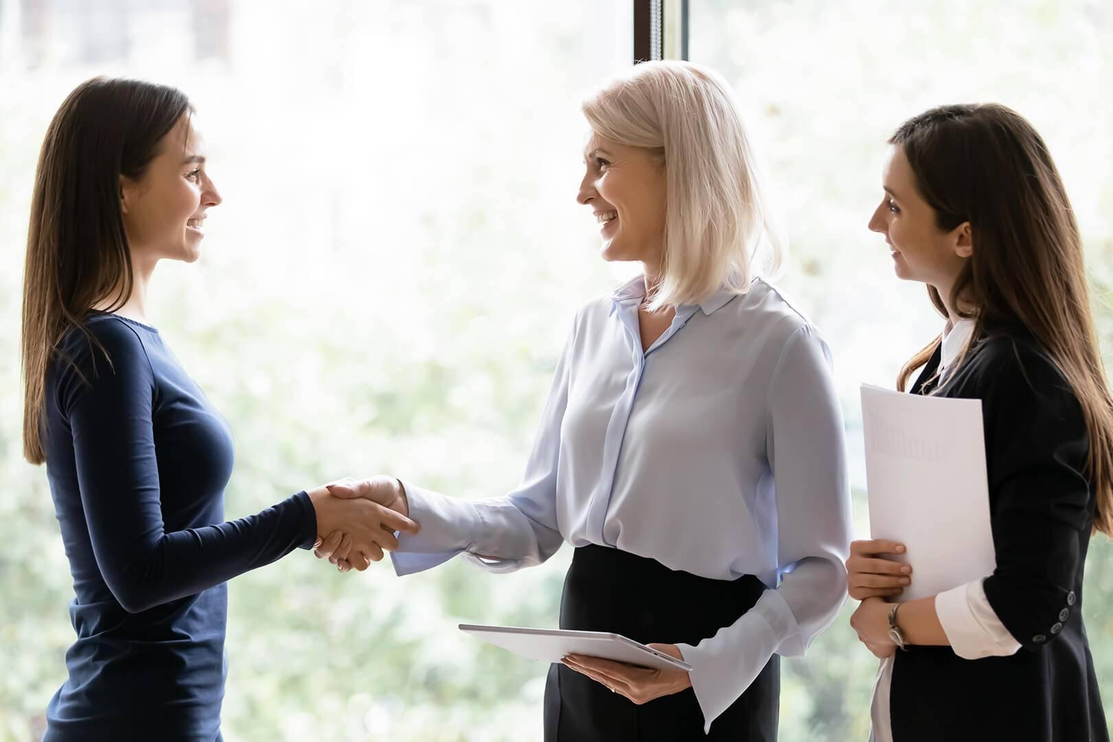 Drei Frauen freuen sich über die Neueinstellung einer Mitarbeiterin