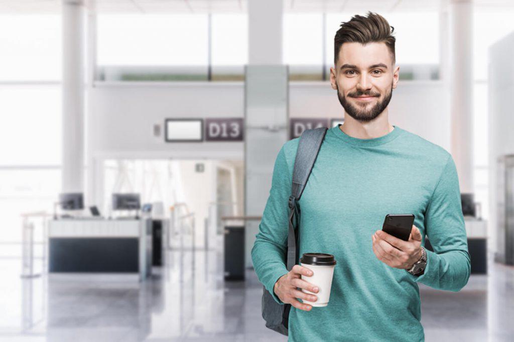 Mann am Flughafen mit Handy in der Hand