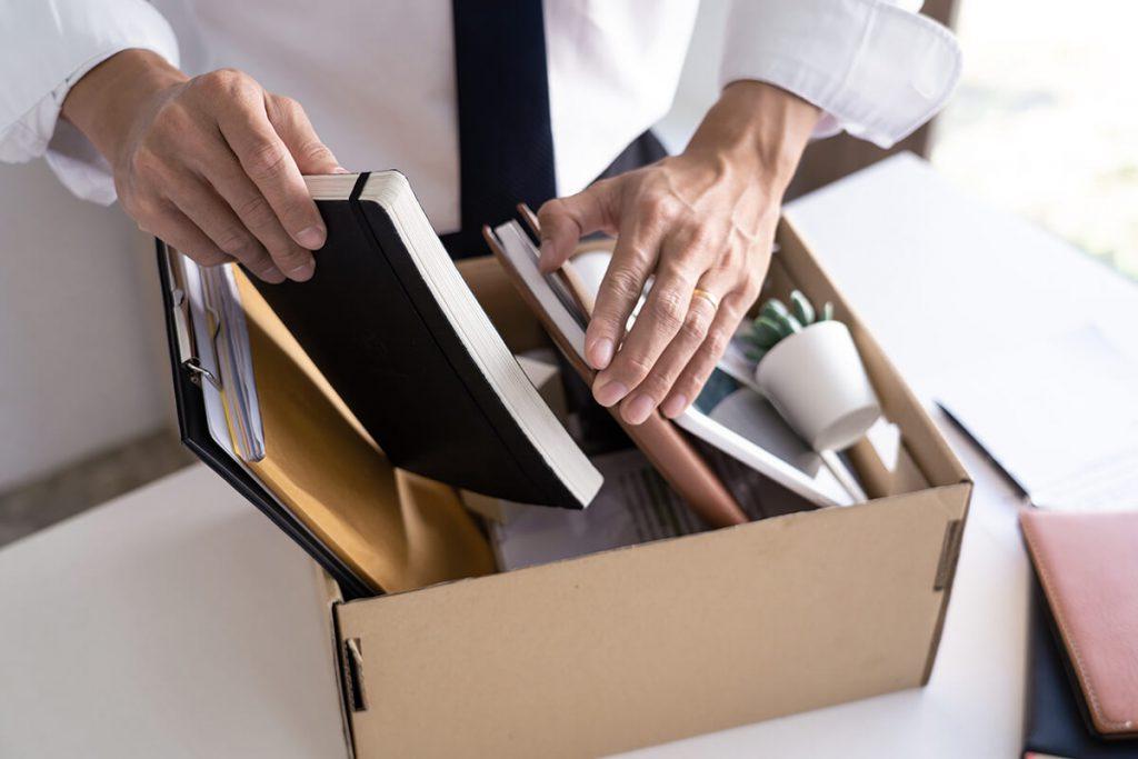 Mann packt Dinge in einen Karton