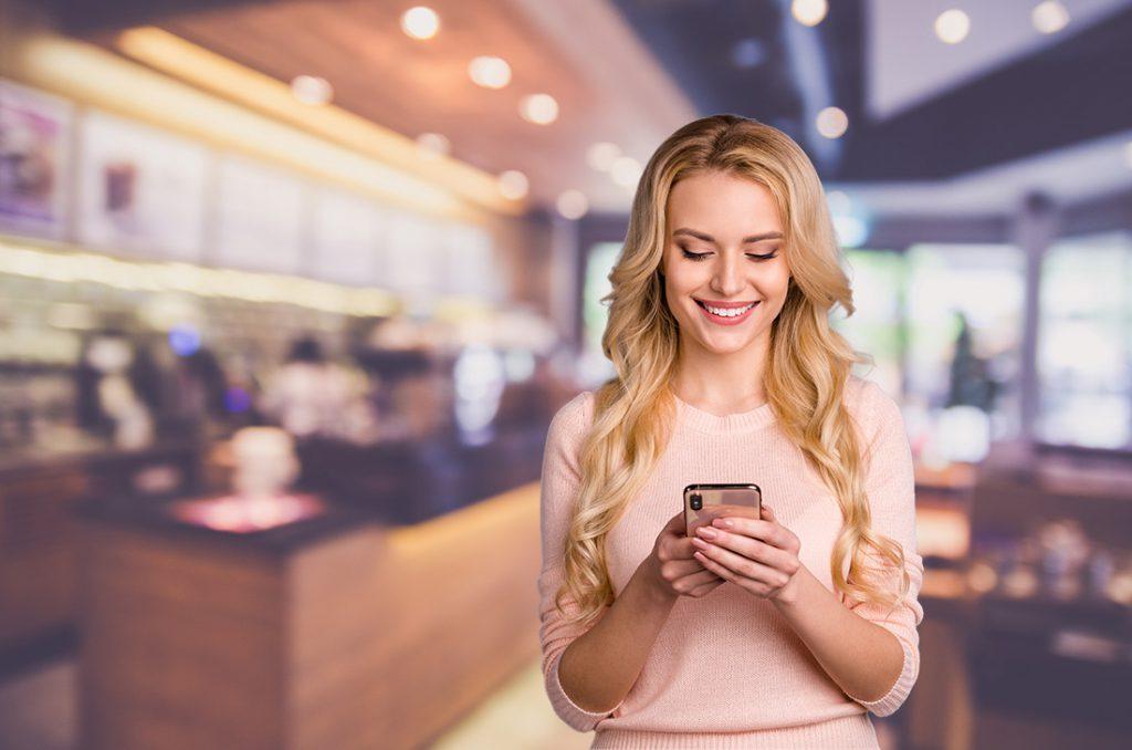 Frau schaut auf Handy in einem Café