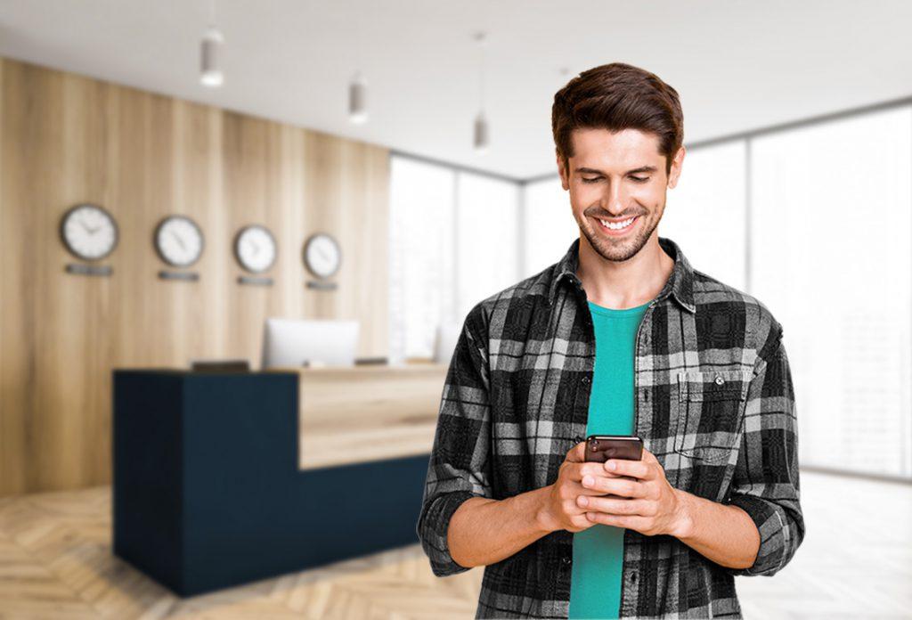 Mann schaut auf sein Handy am Ausgang eines Gebäudes